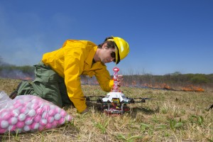 Professor Sebastian Elbaum aligns the fire balls in the chute to ensure a smooth drop. The ball has a chemical powder in it and while airborne, the drone will inject a second chemical. The drone then drops the ball and it bursts into flames within 60 seconds. UNL researchers use a small drone to set prairie burn at Homestead National Monument in Beatrice, NE. April 22, 2016. Photo by Craig Chandler / University Communications